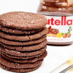 Stack of brown cookies with Nutella jar in background