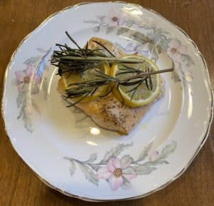 Baked Salmon topped with lemon slices and rosemary on china plate