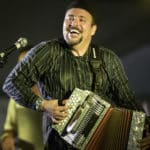 Louisiana Zydeco artist Terrance Simien plays the accordion against a black background.