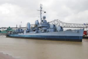 Gray battleship in river with bridge in rear