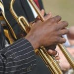 African-American person in blue pin-striped suit holds gold trumpet