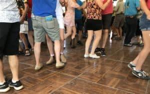 People dancing showing legs only on brown wood floor