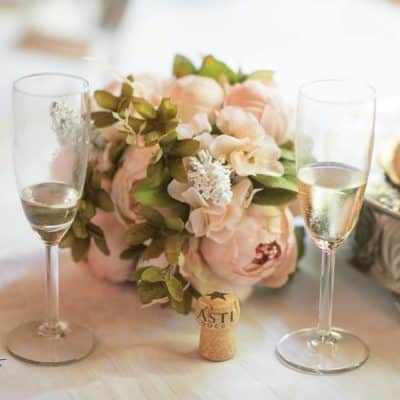 Bouquet of flowers, champagne flutes with champagne, part of cake