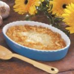 Blue oval dish with baked golden brown grits, wooden serving spoon, yellow sunflowers