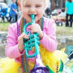 Little girl playing toy trumpet with beads on
