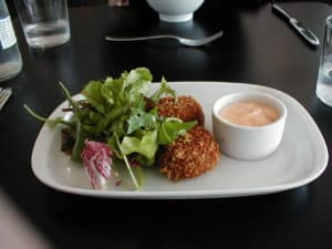 Crab cakes served on white plate with greens and sauce