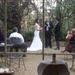 Bride and Groom ceremony looking through panes of window against backdrop of green trees