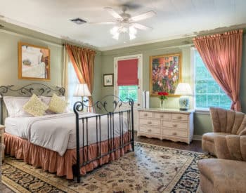 Garden Room with wrought iron queen bed, dresser, sitting area