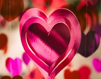 Pink heart on pink and white background of hearts