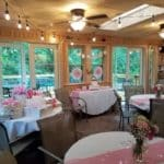Room with round tables decorated in pink and white.