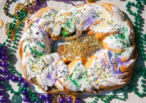 King cake decorated with yellow, purple and green beads