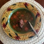 Lentil soup with carrots in beige bowl decorated with red flowers