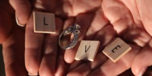 Hand holding scrabble letters L,V,E with silver engagement ring for O