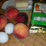 Red peaches, 2 eggs, butter, peach crisp mix on table
