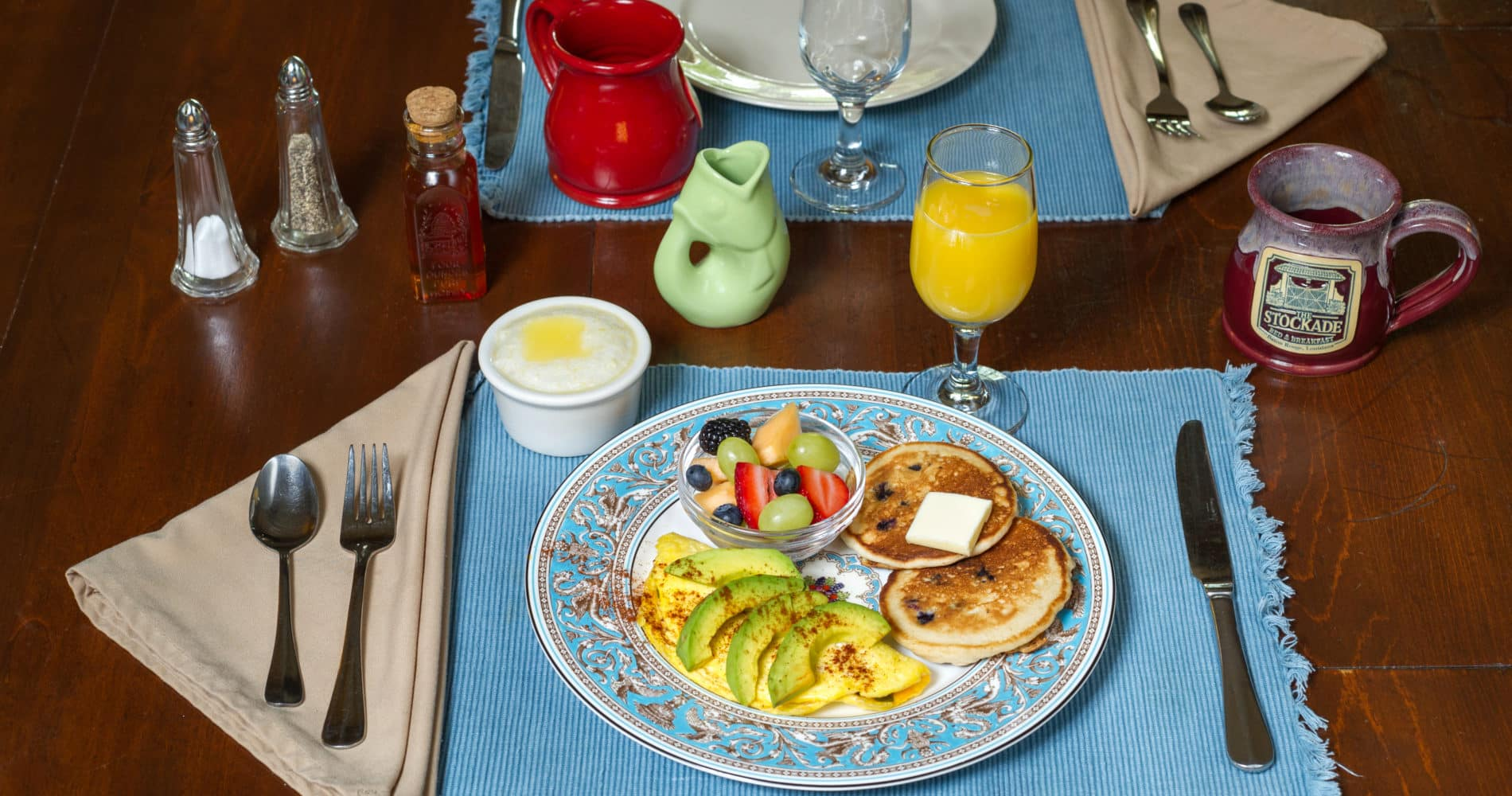 Breakfast of pancakes, avocados, fruit, grits and orange juice