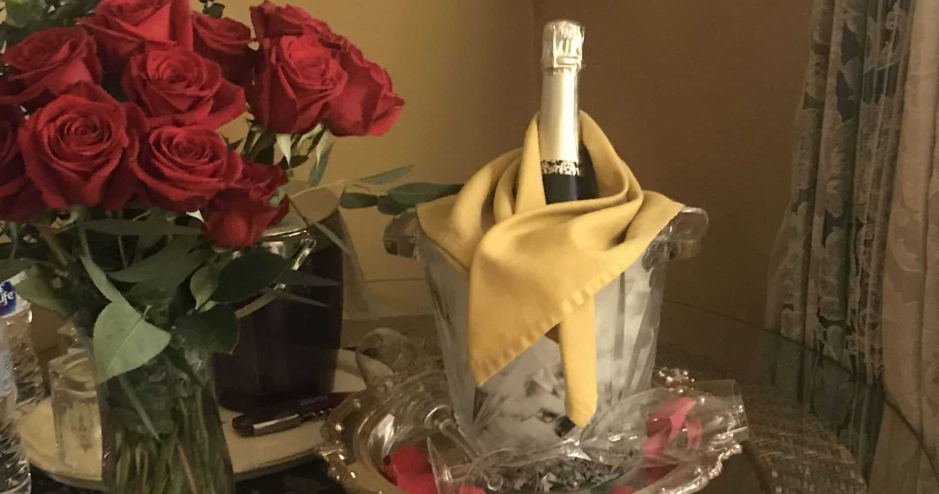 bouquet of red roses and bottle of champagne with 2 champagne flutes