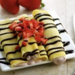 4 crepes on white plate with strawberries and chocolate topping