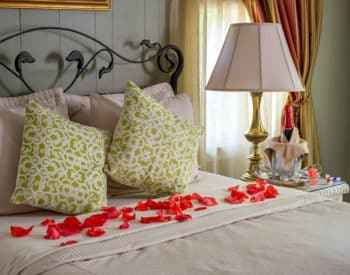 Rose petals on bed with pillows, lamp, bottle of wine
