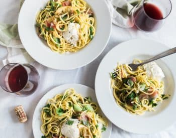 bowls of pasta and 2 glasses of wine