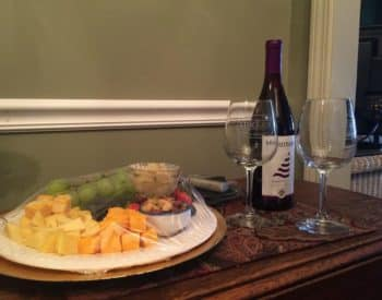 tray of cheeses and fruit, bottle of wine with 2 glasses
