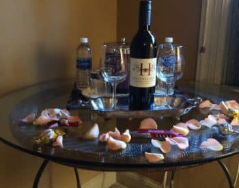 Bottle of wine, wine glasses, rose petals on table