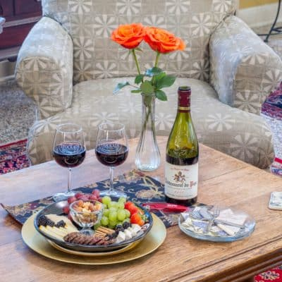 Bottle of wine, 2 wine glasses, hors d'oeuvres, on table with roses in vase