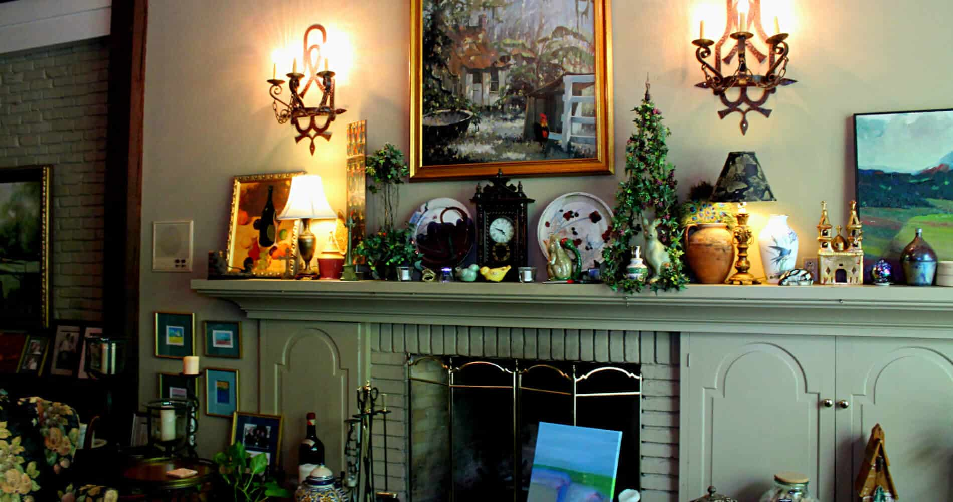 White fireplace with clock and many works of art and painting of Louisiana cabin above fireplace.