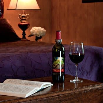 Wine bottle and glasses sitting on a bench at the ebd of a bed with a book