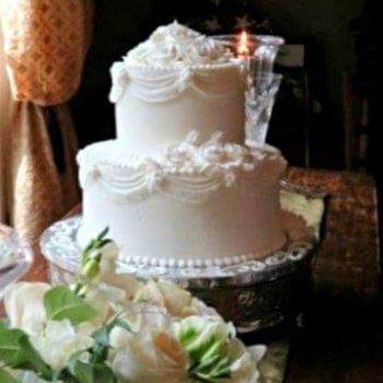 Two Tier White Wedding cake with white rose bridal bouquet