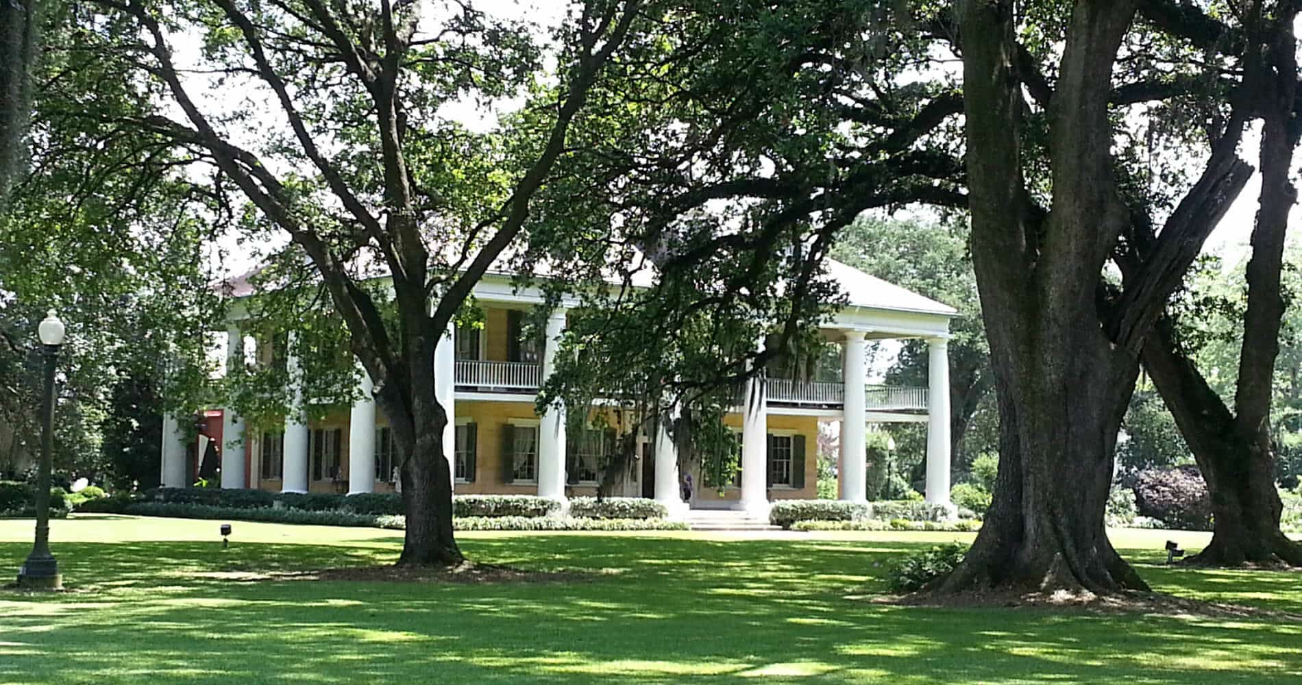 Plantation home with yellow walls, white columns all around, oak trees on property, bright green grass