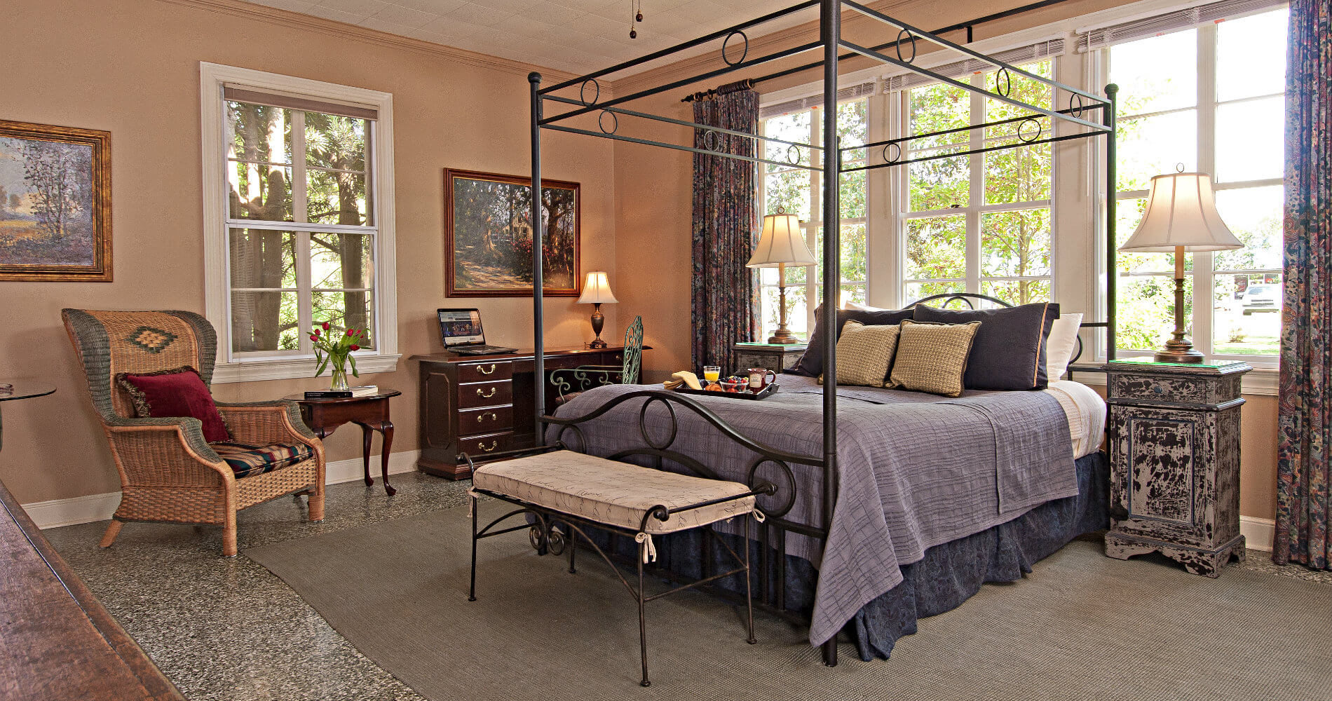 Large bedroom with peach walls and a queen sized iron bed, desk and chairs