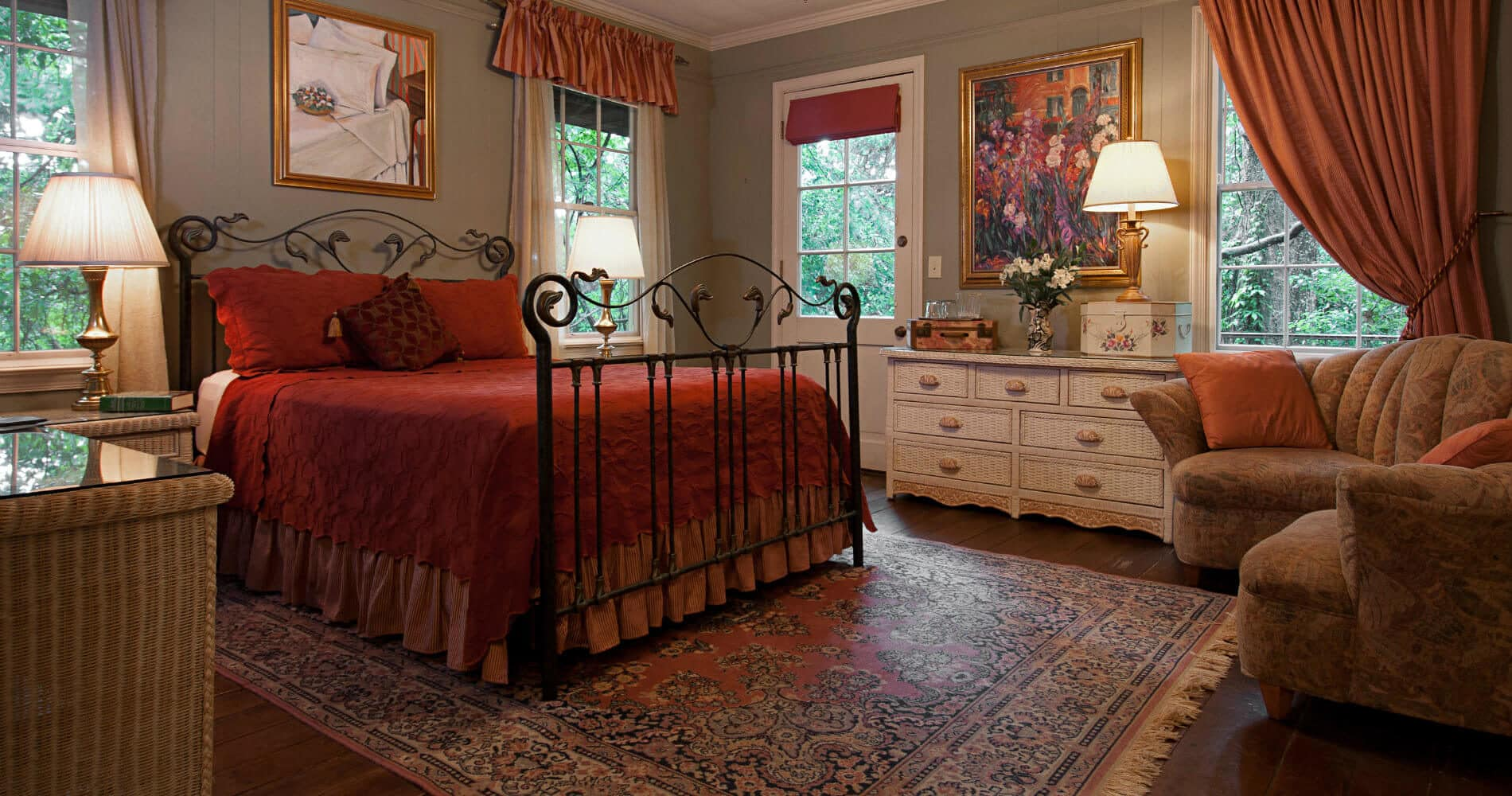 Bedroom with gray walls, red bedspread and curtains and a queen-sized iron bed