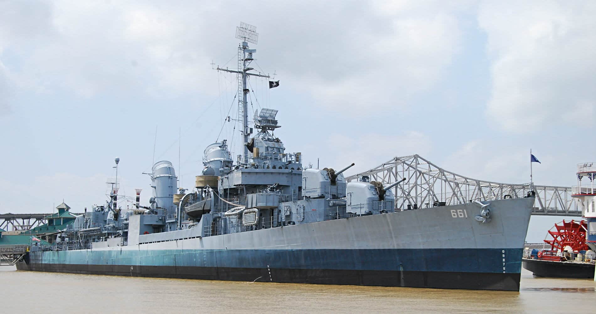 USS KIDD ship docked at the wharf on the muddy Mississippi River with bridge in background.