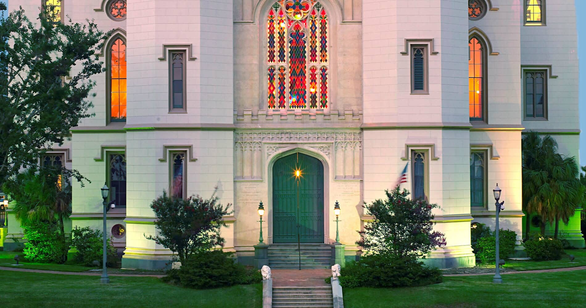 Old courthouse with white walls, stained-glass windows, blue sky, green grass with stairs leading to green front door
