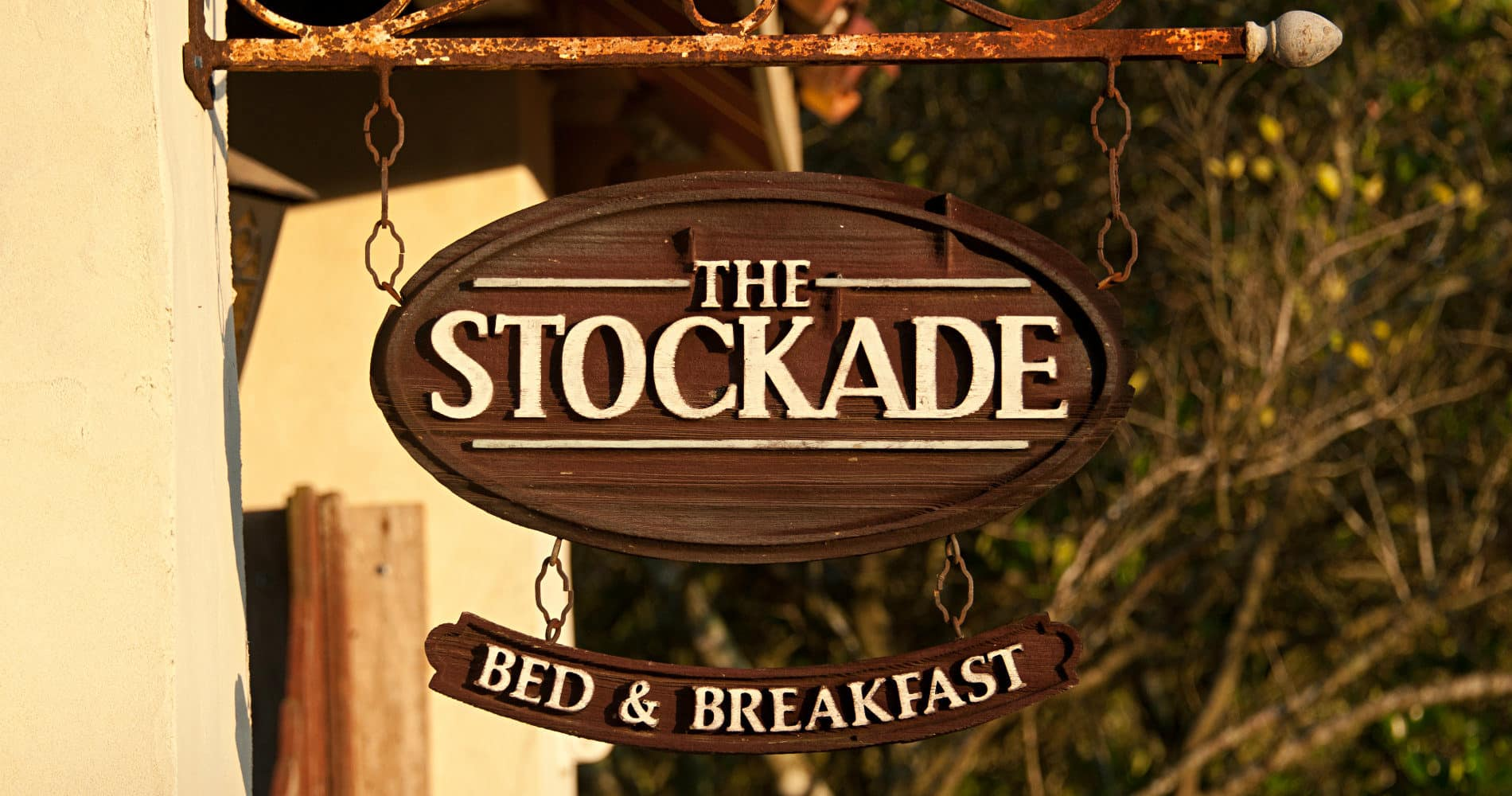 The Stockade sign hanging from ironwork on historic gate, with Bed and Breakfast sign underneath against green trees