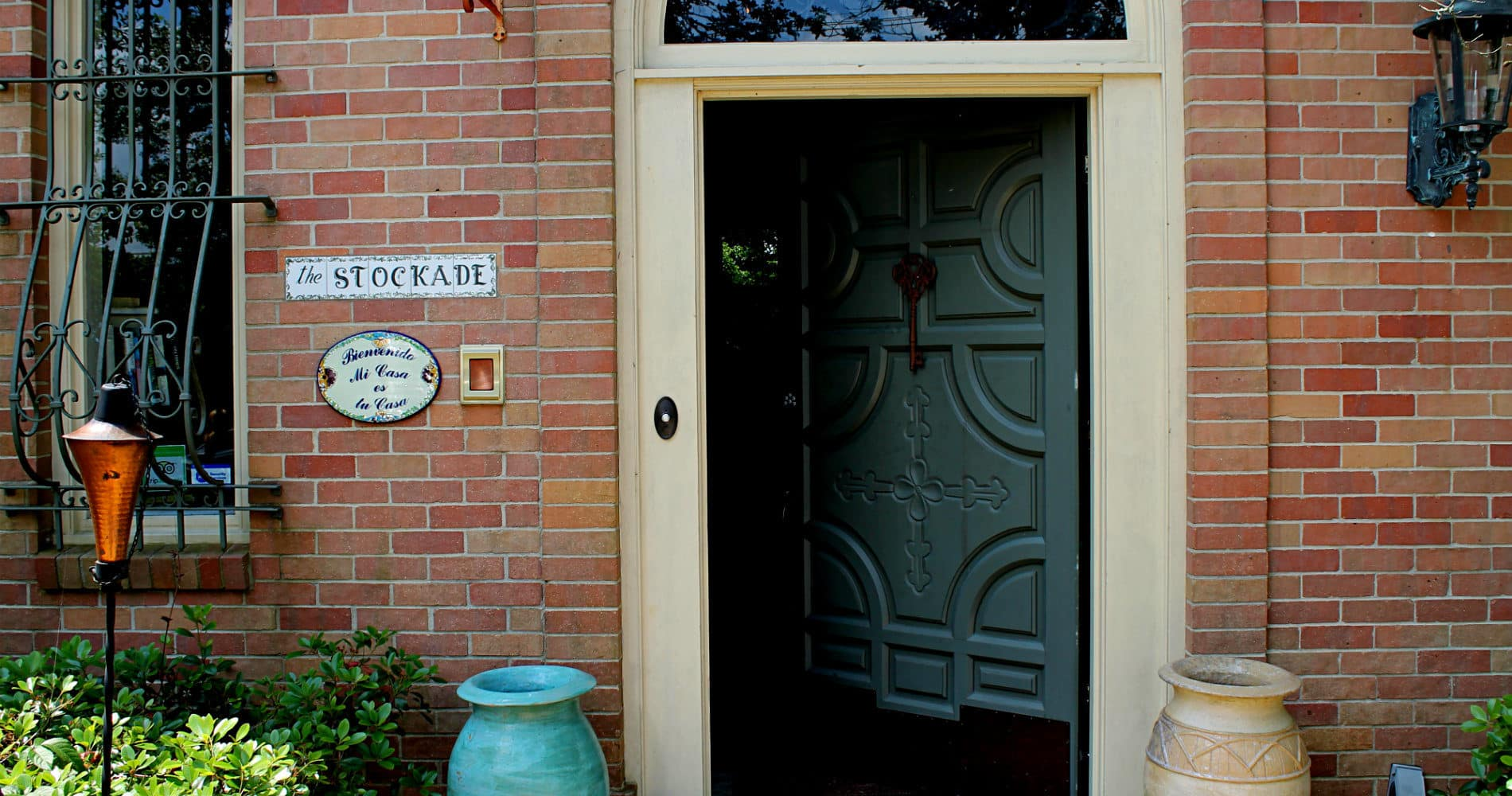 Open aqua blue front door of inn showing The Stockade sign in tile and welcome sign in Spanish to the right of door
