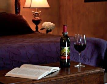 Wood table with bottle of wine, wine glass with red wine, bed behind table with purple beadspread