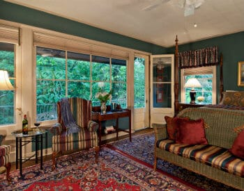 Sitting area of bedroom with dark aqua blue walls, sofa, 2 chairs, door open to outside patio.