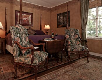 Two tapestry armchairs set at end of large bed on oriental carpet next to a large window with long drapes