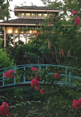 Tea house on hill, arch-shaped bridge in front, flowers all around with red crepe myrtles
