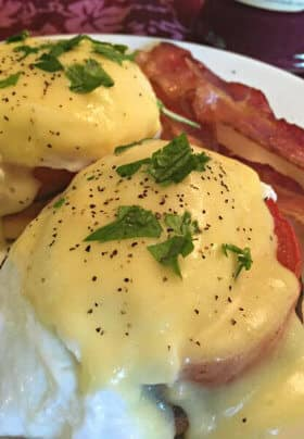 Eggs topped with Canadian bacon, hollandaise sauce, pepper and parsley with a side of regular bacon