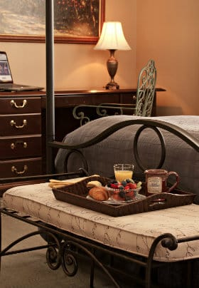 Tray set for breakfast on bench at end of four-poster bead