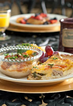 White plate on gold charger with quiche and small glass bowl of grits and grillades, coffee mug and orange juice.