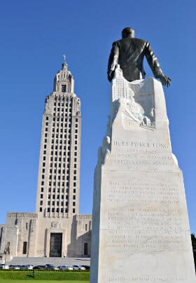 Louisiana State Capitol against a blue sky with back of statue of Huey P. Long