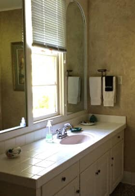 Bathroom with gold walls, white vanity with tiled countertop, 2 mirrors with window in between