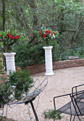 Ceremony site with white pedestals holding red roses, greenery in rear, iron chairs