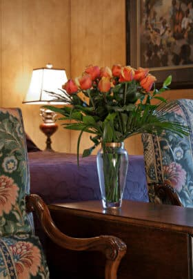 Large bouquet of salmon roses on wooden table between two tapoesty arm chairs at end of bed