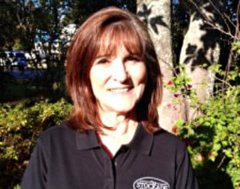 Smiling photo of bookkeeper wearing a black polo shirt with The Stockade logo on the front.