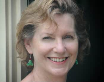 Smiling photo of owner wearing a blue and green dress with green earrings.