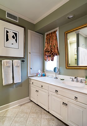 Bathroom with green walls, red floral curtain, vanity with white countertop and mirror